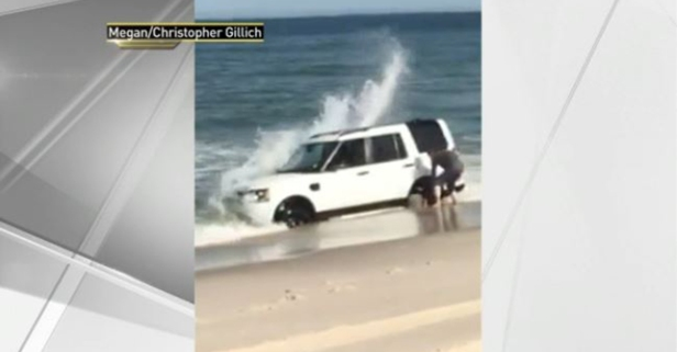 This guy was so busy taking pictures, he didn't see his SUV getting washed into the ocean