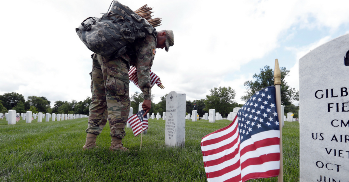 Soldiers complete a 70-year Memorial Day tradition, placing flags on the headstones of fallen service members