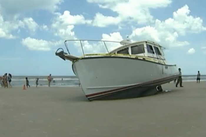 Beachgoers were stunned when a 32-foot boat went ashore at full speed, but here's the weirdest part