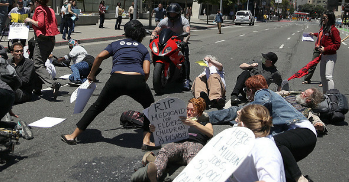 A motorcyclist drove up to Trump protesters lying in the middle of the road and just kept going