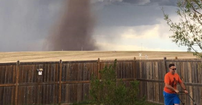 Stunning photo shows a man mowing his lawn in the shadow of a tornado without a care in the world