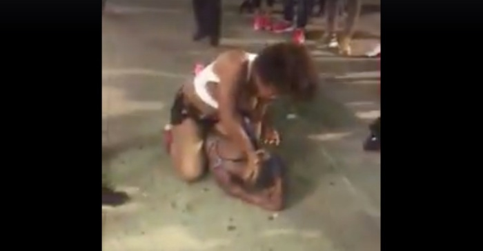 Watch as two women hell-bent on knocking each other out ignore all police activity and keep on fighting