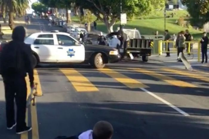 Idiot skateboarder racing down a hill tries to slip around a cop car and gets acquainted with the asphalt