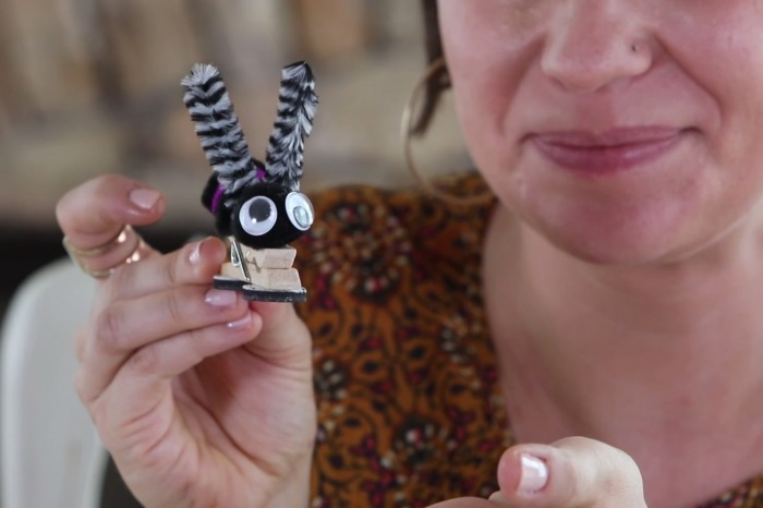 She gathers clothespins, pompoms and googly eyes to make the cutest rainy day craft