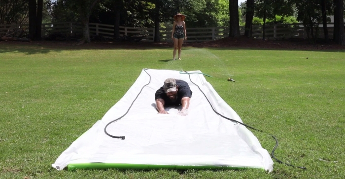 In just a few steps, a huge plastic sheet becomes an irresistibly fun homemade Slip 'N Slide