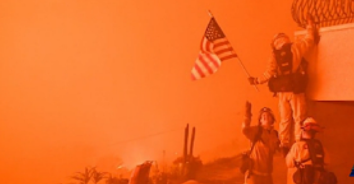 Firefighters pause their battle against a growing wildfire to save Old Glory from the flames