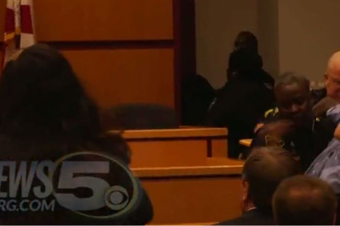An emotional man is stopped by police from approaching his mother during her bond hearing