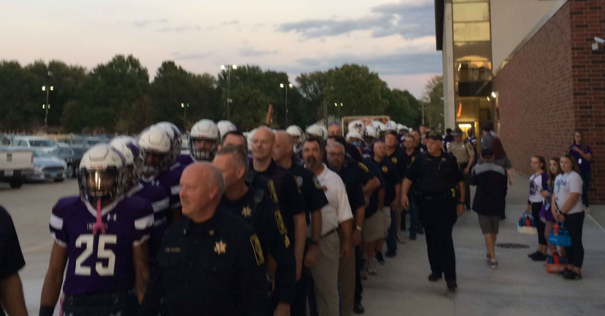 Watch a small town high school football team honor police by marching with them onto the field
