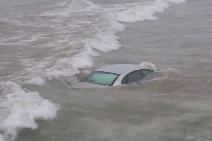 Eerie video shows the moment a lake swallowed a car after the driver lost control on a beachside road