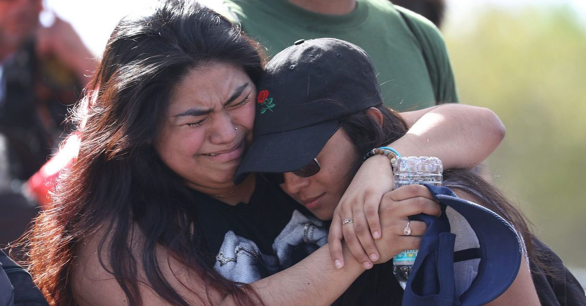 Fernanda Mora (L) an alumna from Deerfield Beach high school and Vallery Cruz a senior at the school hug in front of Marjory Stoneman Douglas High School after walking the 11 miles from school to school in support of the victims of the mass shooting on campus on February 23, 2018 in Parkland, Florida. Police arrested 19-year-old former student Nikolas Cruz for killing 17 people at the high school.